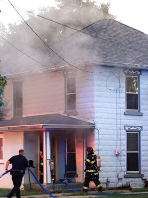 Firefighters work to extinguish a blaze Sunday at a home on Susan Street in Sturgis.