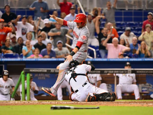 Cincinnati Reds shortstop Zack Cozart (2) is tagged out by Miami Marlins catcher Jeff Mathis (6) at home plate during the eighth inning at Marlins Ballpark. Cozart's play at home plate was overturned from catcher interference.