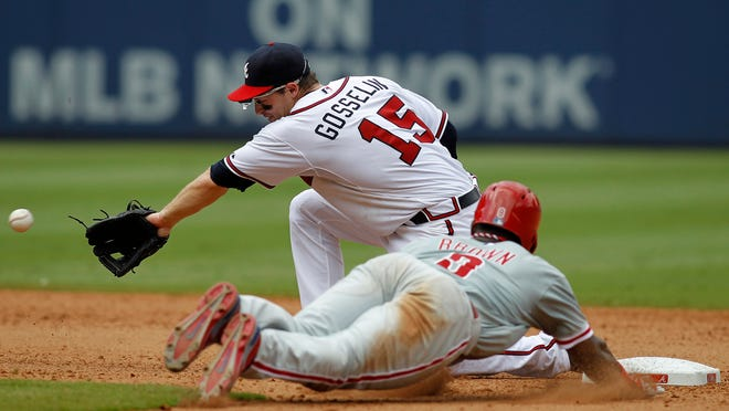 Phillies left fielder Domonic Brown steals a base past Atlanta Braves second baseman Phil Gosselin in the seventh inning Monday at Turner Field in Atlanta.