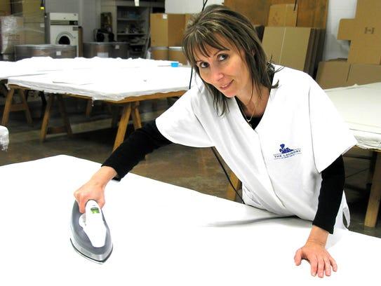 Employee Valentyna Sribnyak irons a vintage tablecloth