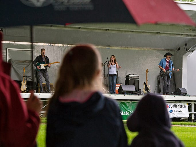 People watch from under an umbrella as the Tumbling Dice plays in the rain at the Lagoon Summer Concert Series on the lawn west of the Lory Student Center on campus at Colorado State University Wednesday, June 18, 2014.