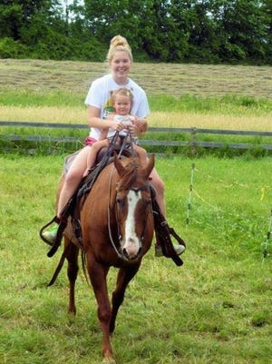 Bunny, the quarter horse, is seen in this file photo with owner Regan Howard's daughter, Jenna Howard, and her granddaughter, Tarah Carten, in an undated photo. A man has been arrested in the death of the horse.