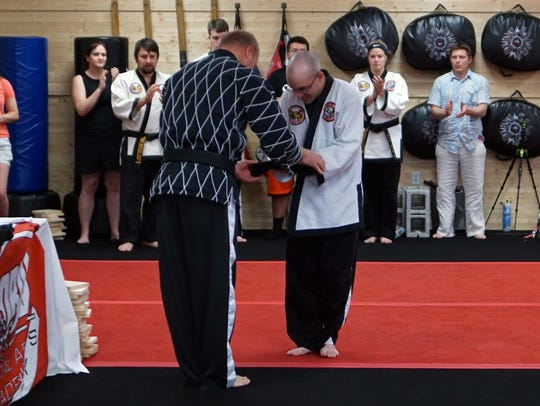 Ed Ogle receives his fifth-degree black belt from instructor