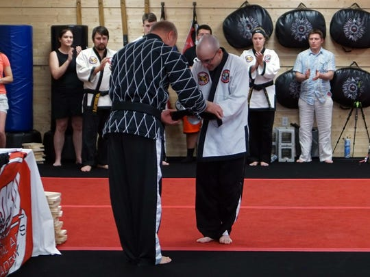 Ed Ogle receives his fifth-degree black belt from instructor Joe Borucki last Saturday at Global Martial Arts Academy in Hampstead, Md.