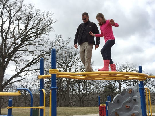Mike McCarthy and his daughter Emily spend some time on playground equipment at Riverside Park Sunday afternoon.