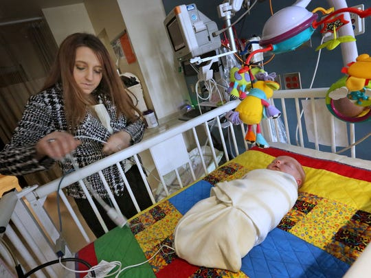 Hailey Swartz re-attaches cords for monitors as her one-month-old daughter Gracelynn sleeps at Franciscan Health Indianapolis, Wednesday, March 21, 2018. Swartz and Gracelynn participate in the Grace Project. The project is a Franciscan Health-based philanthropy that helps drug-addicted mothers and their babies. About 40 families have been helped in the program's two-year history, which provides financial assistance for treatment, as well as living expenses when needed.
