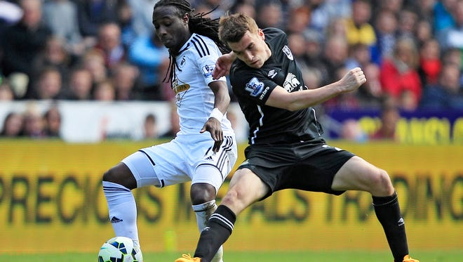 Marvin Emnes of Swansea City (L) in action with Seamus Coleman of Everton.