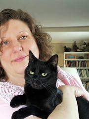 Martini - This is Martini. Her foster mom is our own Aimee Blume with whom she is pictured. She is awesome, and cool and perfect, less like a cat than a small person with black fur who doesn't talk much. She is less than a year old and really likes having a friendly cat companion. She eats Crave grain free food but cannot have people food or she gets an upset tummy! Martini is available for adoption through Another Chance for Animals. She is spayed, microchipped, has all her shots and has been treated for fleas and worms and is in perfect health. Her adoption fee is $30. Contact Aimee at aimeeblume@hotmail.com, or Another Chance for Animals at www.acaevansville.com
