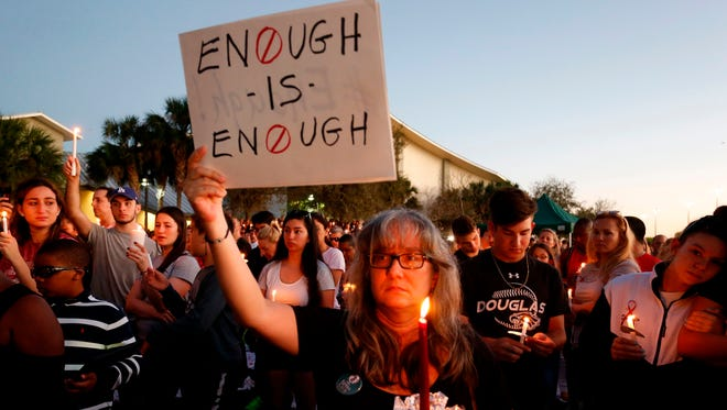 Mourners stand during a candlelight vigil for the victims of Marjory Stoneman Douglas High School shooting in Parkland, Fla.