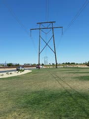 A high-voltage power line passes over grass at Metro