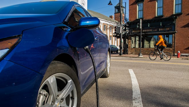 A bundled-up bicyclist on Main Street in Burlington on Wednesday approaches Church Street, where an electric-hybrid Chevy Volt is charging.