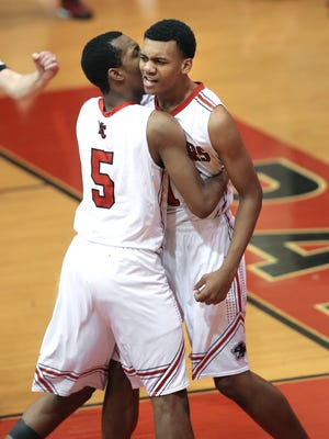 North Central's Antonio Singleton, right, celebrates a slam dunk with teammate Tyrie Johnson against East Chicago Central during the North Central High School Holiday Tournament on Tuesday, Dec. 30, 2014. North Central won 83-81.