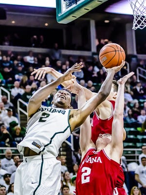 MSU's Javon Bess (left) lays the ball in while being defended by two Indiana players during their game Monday in East Lansing. Izzo eventually would like to have Bess in the starting lineup, so he can bring Bryn Forbes' scoring punch off the bench.