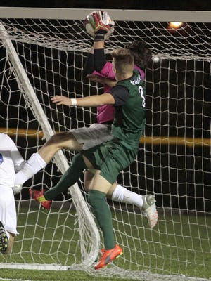 David Hoyle of Hilliard Davidson makes a great save as Bryce Curran of Mason is right there for the header.