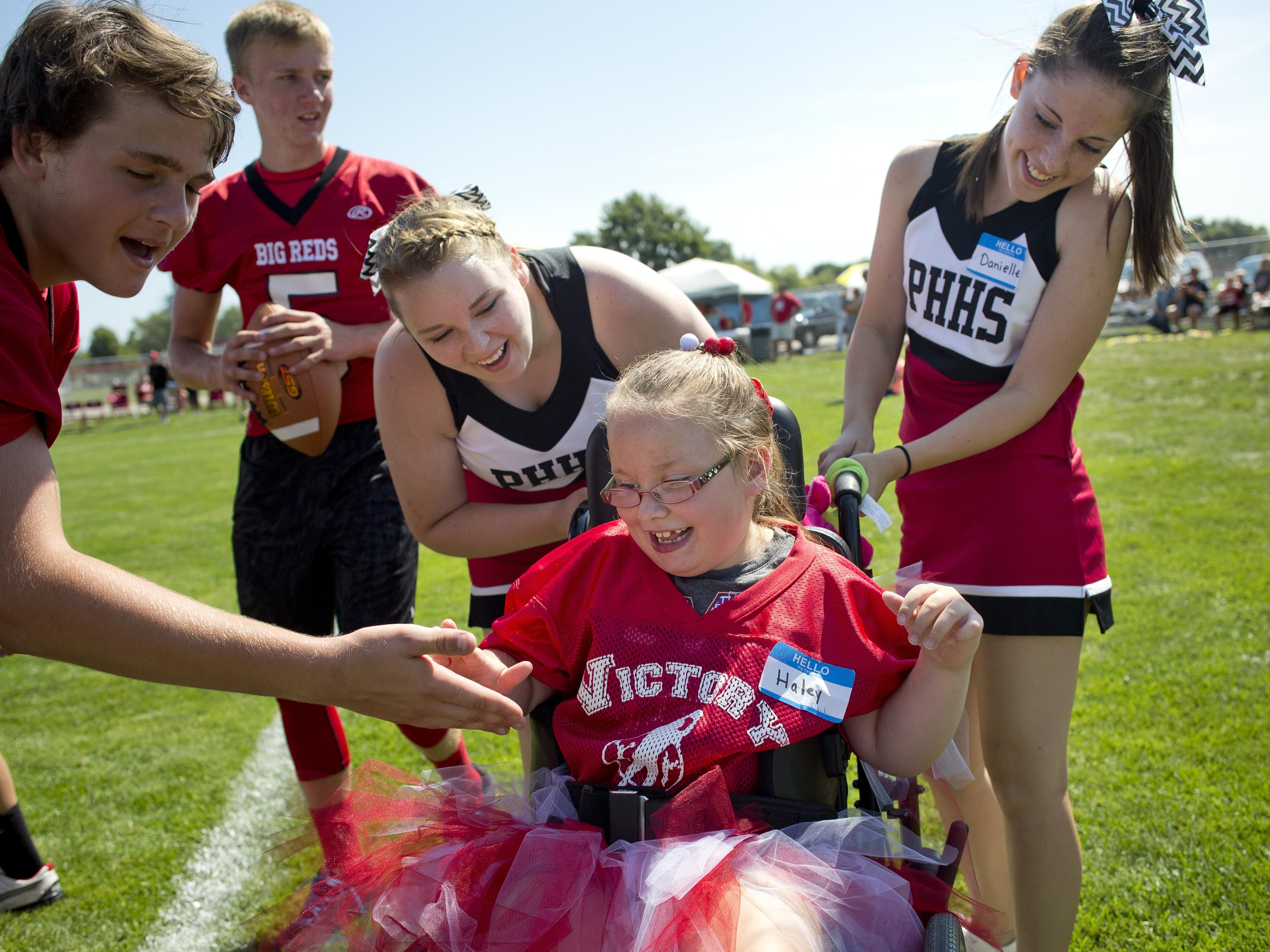 Haley Clark gets high-fives after she scored a touchdown with her mentors Tiffany Peyerk and Danielle Stockwell during Victory Day Saturday, August 15, 2015 in Memorial Stadium at Port Huron High School. The event paired special needs students with mentors from the football and cheerleading teams.