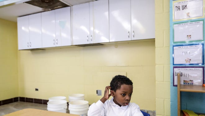 Dean Hayes, 5, of Detroit sits at his desk that is next to a leak coming from the ceiling that consistently drips water into four buckets.