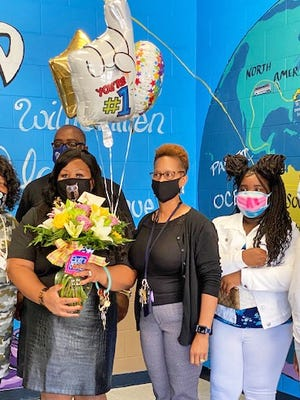 Williston District 29 Teacher of the Year Tamora Parker is surrounded by her family after being surprised at school with the award. Pictured left to right: her mother Gloria Young, Tamora Parker, KEES Principal Nakeisha Baxley, her daughter Ty'Meah Parker, and her son Tylan Parker. Her husband Ernest Parker Jr. is on the back row.