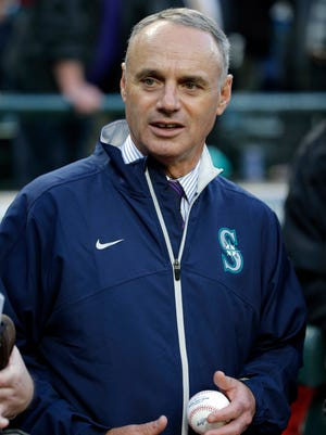 Baseball Commissioner Rob Manfred holds a baseball before a game between the Seattle Mariners and the Los Angeles Angels Wednesday, April 8, 2015, in Seattle. (AP Photo/Ted S. Warren)