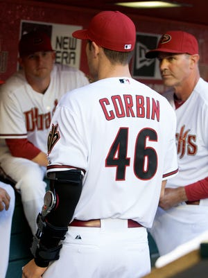 Diamondbacks pitcher Patrick Corbin wears a cast against the San Francisco Giants during opening day baseball game at Chase Field.