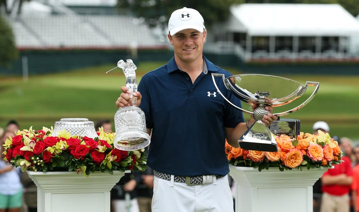 Jordan Spieth with the tournament trophy and FedEx