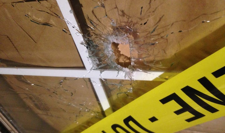 Bullet holes in the window of the room where a pregnant