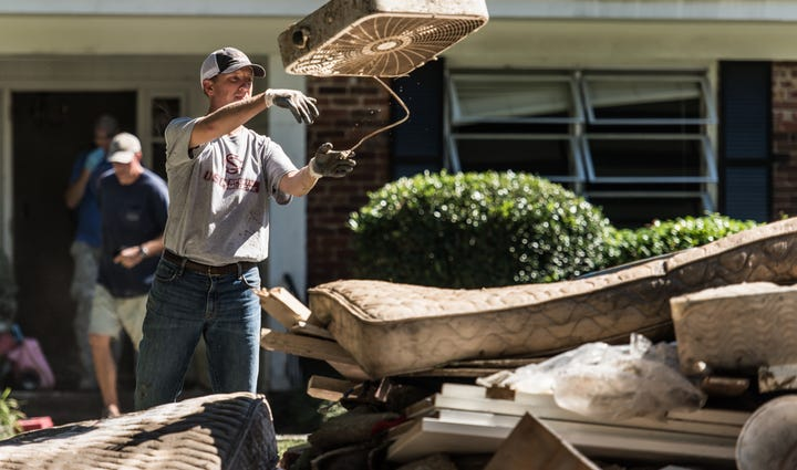 A man throws a fan into a pile of flood-damaged possessions
