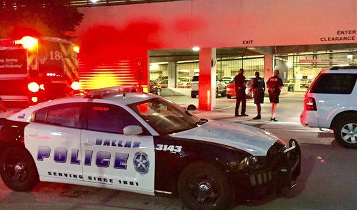 Dallas police investigate the crime scene in the parking