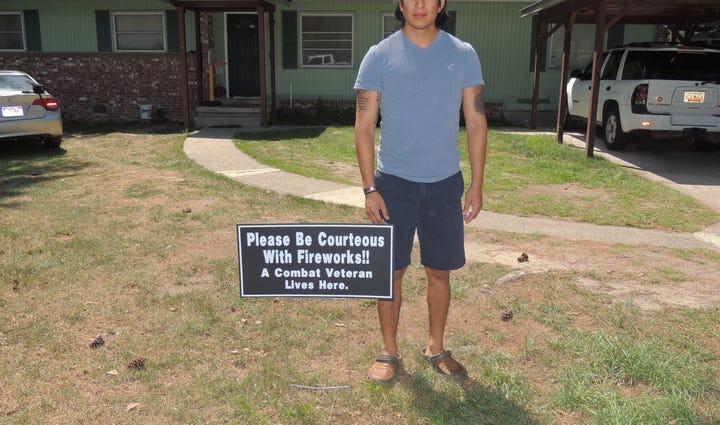 A veteran stands with a sign provided to him by Hidden