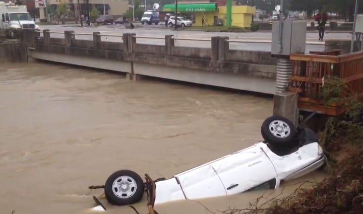 A vehicle sits in the Gills Creek near the intersection