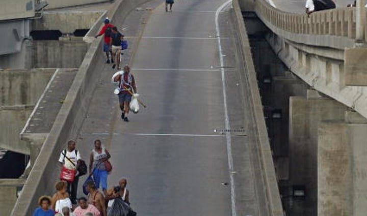 People walk down Interstate 10 near the Superdome in