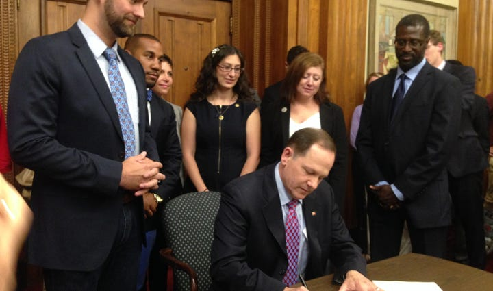Mayor Slay signs the new minimum wage bill.
