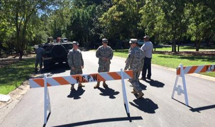 National Guard members stand near a road block not