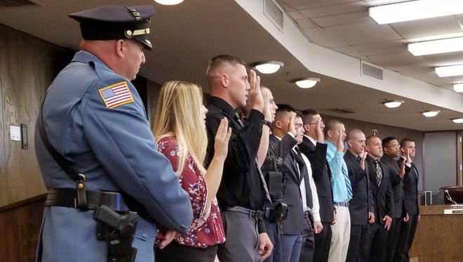 Millville administered oaths Monday morning to 11 police recruits who start training August 7. Police Chief Jody Farabella (left) observes.
