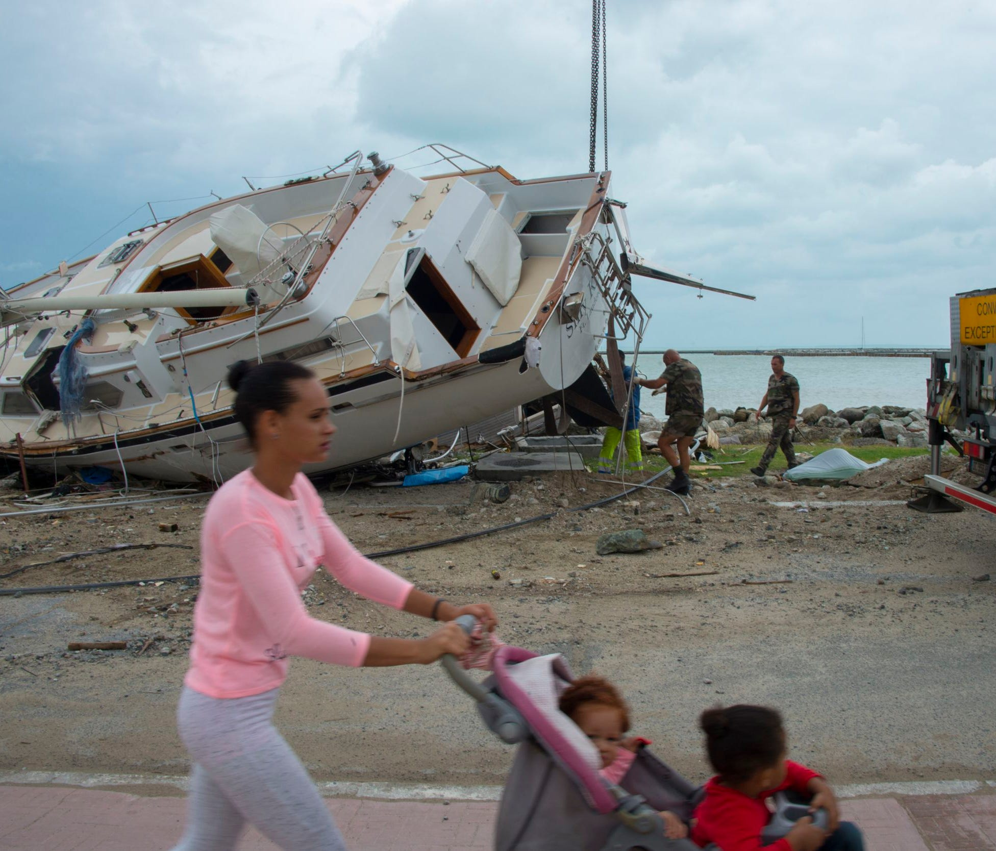 A woman pushes her kids as members of the military help remove damaged boats after the passage of hurricane Irma and Maria in Orient Bay, St. Martin, on Sept. 20, 2017.