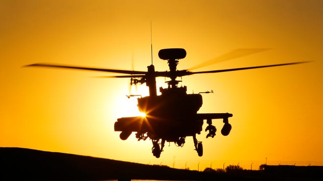 An Apache AH-64E combat helicopter lifts off at the Boeing facility in Mesa.