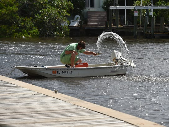 Jesse Mann, of Stuart, throws water from the recent
