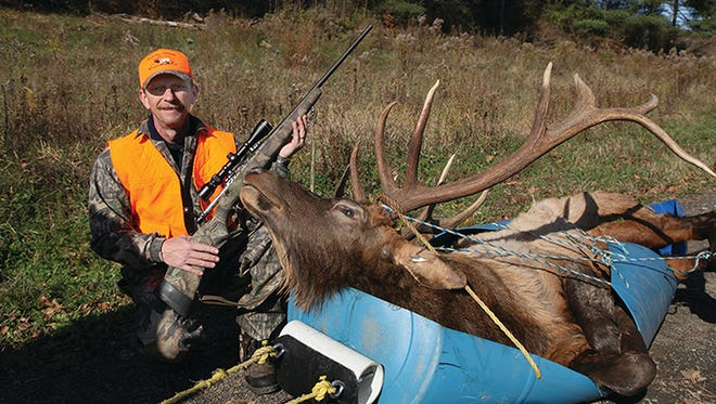 Charles Stone, of Montrose, Pa., by the 6-by-6 bull elk he killed on Nov. 2, the first day of the week long elk-hunting season.
