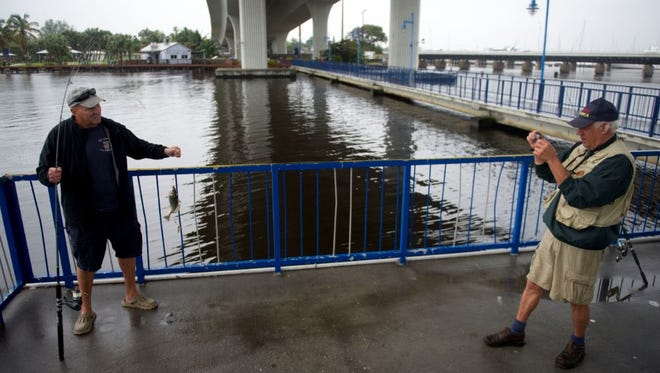 Joe Curcio (left), of Stuart, holds up a fish as his friend, Ralph Brescia, also of Stuart, takes a picture under the Roosevelt Bridge in January 2016 in Stuart.