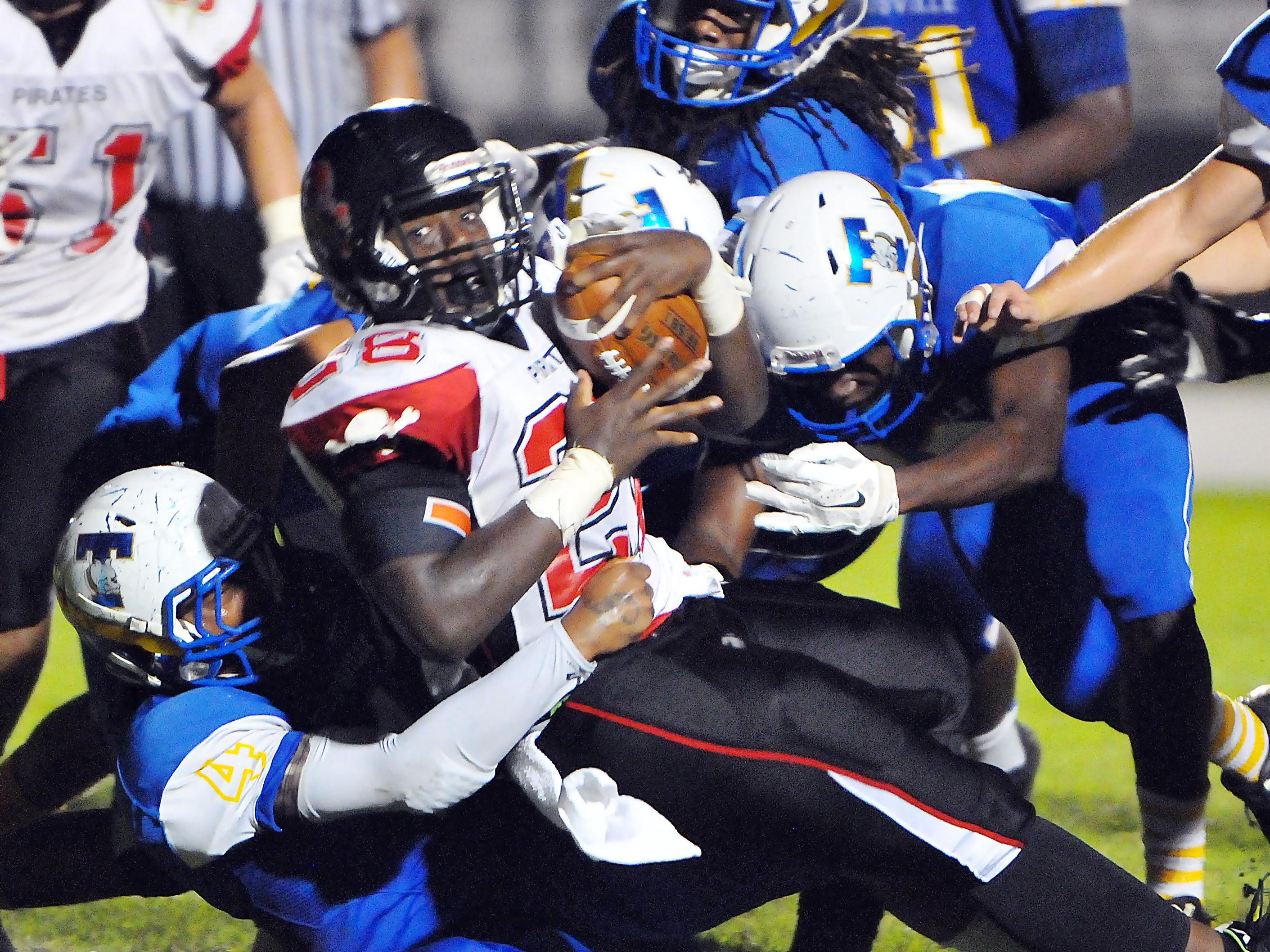Palm Bay High's Tyshaun Rolle (28) drags a Titusville High defender into the end zone for a second quarter touchdown at Titusville High School.