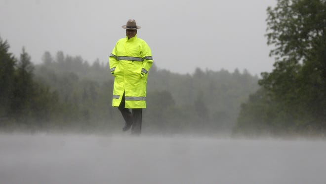 A New York State Police trooper stands in the rain at a roadblock on Sunday, June 28, in Malone, N.Y. The shooting death of one escaped killer brought new energy to the three-week hunt for a second escaped murderer in the United States as helicopters, search dogs and hundreds of law enforcement officers converged on a wooded area 30 miles from Clinton Correctional Facility.