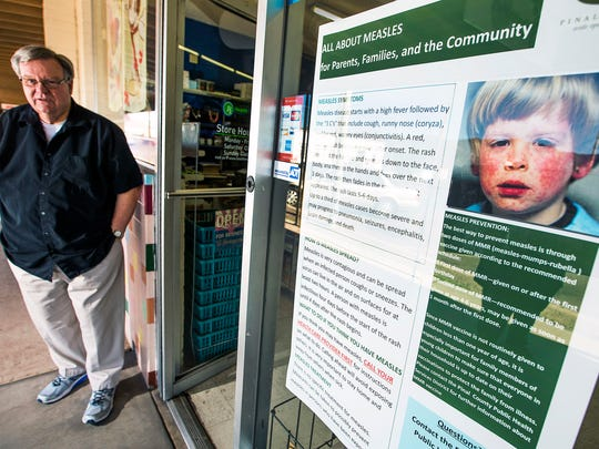 Kearny Health Mart, where Jay Mahoney is a pharmacist, displays a sign in the window warning customers to be on the lookout for measles symptoms. The small Arizona town is reeling from a measles outbreak, which started when an unvaccinated family contracted the disease during a December visit to Disneyland.