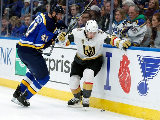 St. Louis Blues' Robert Bortuzzo (41) and Vegas Golden Knights' Cody Eakin (21) chase after a loose puck along the boards during the first period of an NHL hockey game Thursday, Jan. 4, 2018, in St. Louis. (AP Photo/Jeff Roberson)