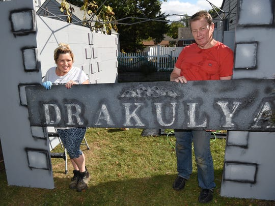 Marisol Mahlmeister, left, and Bill Mahlmeister, right, of Fishkill, hold up one of the signs to the Halloween display on their lawn.