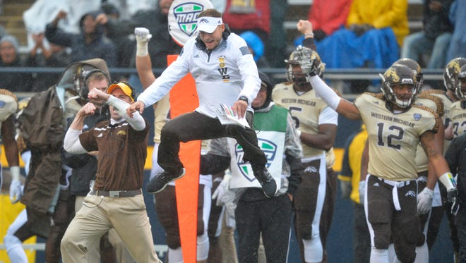 Western Michigan football coach P.J. Fleck, center, leaps in the air after a Toledo turnover on downs Nov. 27, 2015, in Toledo.