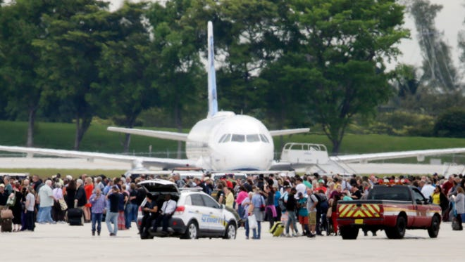People stand on the tarmac at the Fort Lauderdale-Hollywood International Airport after a shooter opened fire, Friday, inside a terminal of the airport.