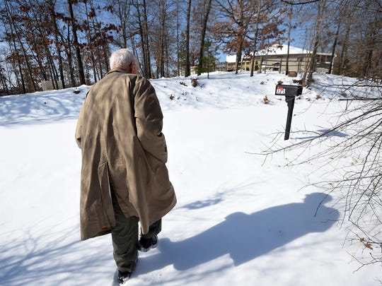 Pierce Ripka walks to his mailbox to check road conditions. It's obvious that Baxter County Road 176 had yet to be touched by a snow plow on Tuesday afternoon.