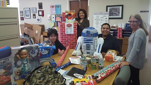 From left, Linda Mickey, executive director of San Juan United Way; Priscilla Williams, finance director of San Juan United Way; Tyler Frazier, manager at Arizona Public Service Co.'s Four Corners Power Plant; and Lillian Rose, campaign director of San Juan United Way are pictured among donated items at San Juan United Way during the Community Christmas drive.
