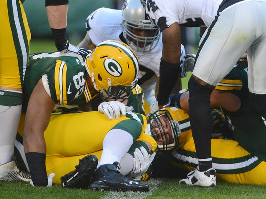 Packers center JC Tretter holds his knee on the goal line after he was injured on a running play in the first quarter Friday against the Raiders at Lambeau Field.