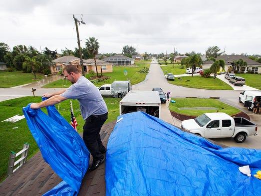 Ryan Tomten spreads tarp on the roof of Cheryl Cooper's