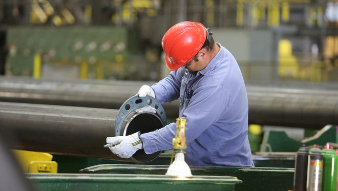 Steve Mayer examines a steel pipe manufactured at TMK Ipsco's production facility in Wilder. By next month, roughly 85 percent of the plant's workers will be on layoffs.
